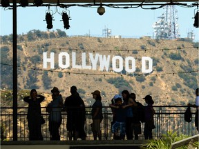 LOS ANGELES, CA - JUNE 28:  Tourists are slihouted against the distroted Hollywood sign from rising heat waves during a major heat wave in Southern California on June 28, 2013 in Los Angeles, California. Temperatures are expected to be in the triple digits in most areas of Southern California. According to the national Weather Service, the heat wave is expected to linger into early next week prompting heat advisories and opening of cooling centers.  (Photo by Kevork Djansezian/Getty Images) ORG XMIT: 171962694