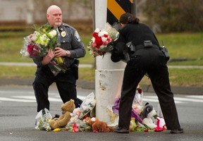 Police officers remove flowers from a busy intersection December 16, 2012 in Newtown, Connecticut. The officers said they were afraid the memorial may cause a traffic hazard. The people of Newtown, soon to be joined by President Barack Obama, poured into churches Sunday to pray for the 20 children and seven adults slaughtered in one of the worst ever US shooting massacres. The small Connecticut town led the nation in mourning 48 hours after Adam Lanza burst into Sandy Hook Elementary School and murdered two roomfuls of six- and seven-year-old children, the school principal and five other female staff. From early Sunday churches filled and the town Christmas tree became an impromptu place of remembrance, with people pausing every few minutes to pray and cross themselves under a light snowfall.   AFP PHOTO/DON EMMERT
