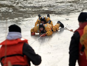 Amherstburg firefighters Bill Scott and Mario Fiorito take part in a water rescue exercise in the Rivere Canard on Saturday Feb. 16, 2013 in Amherstburg.   Windsor-Essex EMS,  Tecumseh Fire Service and Amherstburg Fire Service participated in the annual training to familiarize the first responders with ice and water rescue operations.  (JASON KRYK/ The Windsor Star)