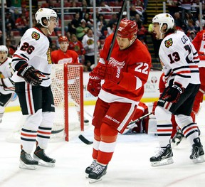 Chicago's Jeremy Morin, left, celebrates his goal with teammate Daniel Carcillo, right, as Detroit's Jordin Tootoo skates away Sunday, March 31, 2013, in Detroit. The Blackhawks defeated the Red Wings 7-1. (AP Photo/Duane Burleson)