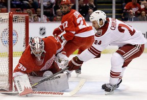 Detroit goalie Jimmy Howard, left, stops a shot by Phoenix forward Kyle Chipchura with Kyle Quincey in the background. (AP Photo/Paul Sancya)