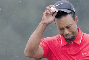 Tiger Woods dodges raindrops after putting on the final green at the 77th Masters golf tournament at Augusta National Golf Club last month. He also dodged disqualification after officials called a two-stroke penalty for an illegal drop at the 15th hole. (Photograph by: Getty Images Files , The Associated Press)