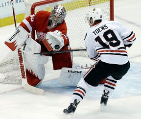 Detroit goalie Jimmy Howard, left, makes a save on Chicago's Jonathan Toews in Game 4 of the Western Conference semifinal. (AP Photo/Paul Sancya)