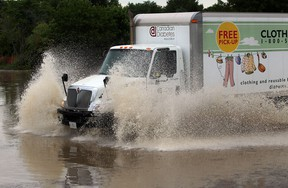 Vehicles continue to travel along Laurier Drive in LaSalle following heavy rains overnight,  Thursday June 13, 2013. (NICK BRANCACCIO/The Windsor Star)