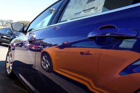 A Ford Focus is reflected on the side of another Focus in a new car lot. (Getty Images files)