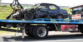Myers Towing removes a Toyota Corolla from a ditch on South Service Road near Jefferson Avenue Thursday June 27, 2013.  Towing crews were busy with the second vehicle, a Mack tractor-trailer rig with a full load.  Windsor police were at the scene investigating. (NICK BRANCACCIO/The Windsor Star)