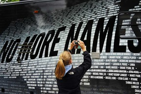 In this file photo, Lindsay Knauf takes a picture of a bus bearing some of the over 6,000 names of people killed by gun violence since the massacre in Newtown at a remembrance event on the six-month anniversary of the massacre at Sandy Hook Elementary School on June 14, 2013 in Newtown, Ct. (Spencer Platt/Getty Images)