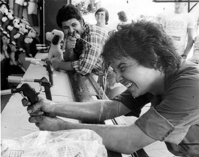 Jim Gatto gets a squirt in the face from fellow Canadian Tire Ltd. employee Jim Baz Thursday while visiting a carnival booth set up beside the Windsor Art Gallery on Riverside Drive June 28, 1978. (JOHN COCHRAN/The Windsor Star)