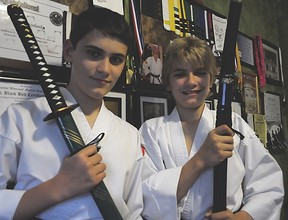 Evan Kozolanka (left) and his older brother Zack (right) pose with samurai swords in their Tecumseh home Sunday, June 2 in front of a wall displaying many awards and medals they have won in the South Korean martial art of hapkido. (Photo by/Rob Benneian)
