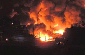 Flames shot several metres into the air after a train carrying crude oil derailed in the Quebec town of Lac-Megantic early Saturday, July 6, 2013. (Anne-Julie Hallée , YouTube)