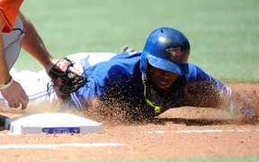Toronto's Jose Reyes, right, dives safely back into first base against the Houston Astros Sunday July 28, 2013 in Toronto. (THE CANADIAN PRESS/Jon Blacker)
