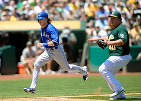 Toronto's Colby Rasmus , left, scores on a passed ball beating the throw back to Oakland pitcher Bartolo Colon July 31, 2013 in Oakland. (Thearon W. Henderson/Getty Images)
