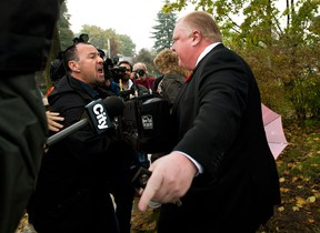 City of Toronto Mayor Rob Ford, right, pushes members of the media off his property as he leaves his home in Toronto on Thursday, Oct. 31, 2013. THE CANADIAN PRESS/Nathan Denette