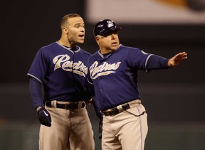 San Diego first base coach Rick Renteria, right, holds back Scott Hairston after being called out for interference against the San Francisco Giants  in San Francisco. (Ezra Shaw/Getty Images)