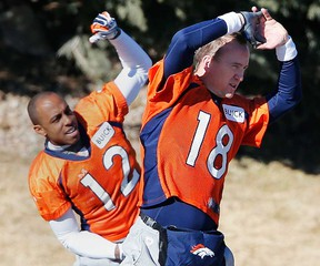 Broncos QB Peyton Manning, right, and wide receiver Andre Caldwell stretch during practice in Englewood, Colo., Friday, Jan. 17, 2014. The Broncos host the New England Patriots Sunday for the AFC championship. (AP Photo/Ed Andrieski)