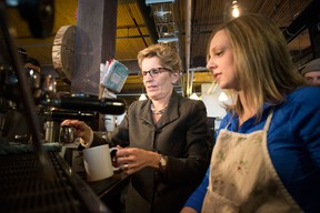 Ontario Premier Kathleen Wynne, left, is shown how to brew a cup of coffee at 'The Coffee Pub' by owner Erin Cluley, on Thursday,  January 30, 2014. The premier announced Ontario's minimum wage will be increased to $11 an hour effective June 1, up 75 cents. (THE CANADIAN PRESS/Chris Young)