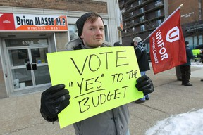 Travis Barron leads a small group of protesters in front of the office of Windsor-West MP Brian Masse in Windsor on Wednesday, February 26, 2014. The group Vote With Windsor is urging Masse to support the federal budget.                 (TYLER BROWNBRIDGE/The Windsor Star)