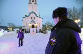 A policeman watches a believer leaving the Cathedral of the Resurrection of Christ in Yuzhno-Sakhalinsk on Sunday, Feb. 9, 2014. Law enforcement officers detained a man, who worked as a security guard, and were trying to determine why he attacked the Russian Orthodox cathedral in the city of Yuzhno-Sakhalinsk, the federal Investigative Committee said in a statement. A gunman opened fire Sunday in a cathedral on Russia's Sakhalin Island in the Pacific, killing a nun and a parishioner and wounding six others, investigators said. Concerns about security in Russia are especially high because of the Winter Olympics in Sochi, but there was no apparent connection to the games. Sakhalin Island is about 7,500 kilometers (more than 4,500 miles) from Sochi. (AP Photo/ Dmitriy Sindyakov)