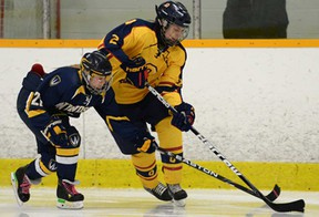 Windsor's Bree Polci, left, and Queen's Alisha Sealey battle for the puck during their OUA playoff game Thurs. Feb. 13, 2014, at South Windsor Arena. (DAN JANISSE/The Windsor Star)