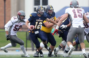 Windsor quarterback Austin Kennedy, centre, scrambles out of the pocket against the Guelph Gryphons at Alumni Field. (DAX MELMER/The Windsor Star)