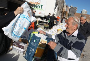 People pick up turkeys donated by Andy Jun, owner of Renu Kitchen Refacing, at the downtown Mission, Saturday, Oct. 11, 2014.  Potatoes, turnips, peppers, and desert were also given out to 250 people.  Another 250 turkeys were donated by Diane and Guy DaMarco and were given out at the Unemployed Help Centre.  (DAX MELMER/The Windsor Star)