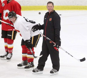 Calgary Flames goalie coach Clint Malarchuk, right, takes a break during Flames practice in 2011.  (Leah Hennel/Calgary Herald)