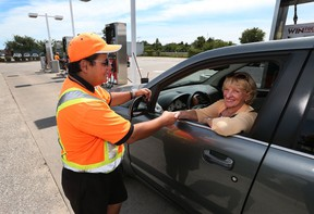Motorist Linda Iler, from Windsor thanks Dave's Big Chief gas station attendant Nadal Eljayeh for his service at the Big Chief gas station on Tecumseh Road East in Tecumseh, Ontario on August 6, 2015. (JASON KRYK/The Windsor Star)