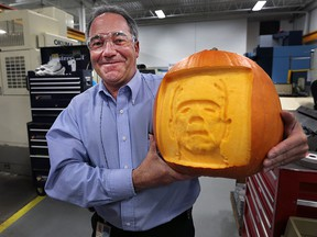 Mike Ouellette, skills trades training coordinator with Valiant International in Windsor, Ont. displays a pumpkin with a 3D image of Frankenstein. The high-tech carving was done with a CNC machine. The company is offering to carve custom logos into pumpkins to raise funds for a local student robotics group.