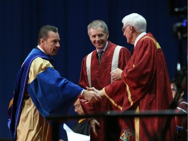 FCA Canada CEO Reid Bigland, left, is congratulated by University of Windsor chancellor Ed Lumley, right,  and University of Windsor president and Alan Wildeman after  Bigland received an honorary doctor of laws degree during the fall University of Windsor convocation on October 17, 2015.
