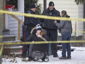 Two unidentified people embrace outside a house at 395 Curry Ave., where Windsor police are investigating a house fire, Saturday, February 13, 2016.