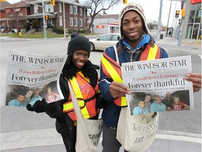 WINDSOR, ON. NOV. 27, 2014. Goodfellows and University of Windsor track team members Esinam Ayesu-Attah (L) and Arren Yound sell newspapers on Wyandotte St. W. in Windsor, ON. on Thursday, Nov. 27, 2014.  (DAN JANISSE/The Windsor Star)