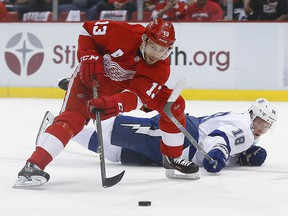 Tampa Bay Lightning left wing Ondrej Palat (18) tries to defend Detroit Red Wings center Pavel Datsyuk (13) duringh the first period of Game 4 in a first-round NHL hockey Stanley Cup playoff series, Tuesday, April 19, 2016, in Detroit.