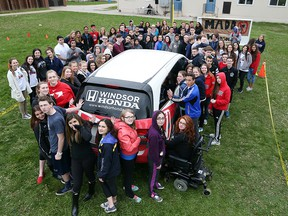 """Holy Names Catholic High School students take part in a day-long fundraiser in suppert of MADD Windsor & Essex County. The event called """"Hands on the Van"""" fundraiser challenged students pay $5 to put their hands on a van and remain there for the day. (JASON KRYK/WINDSOR STAR)"""