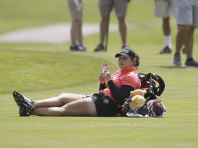 Ariya Jutanugarn, of Thailand, takes a break on the sixth fairway as play backs up during the third round of the LPGA Volvik Championship golf tournament at the Travis Pointe Country Club, Saturday, May 28, 2016, in Ann Arbor, Mich.