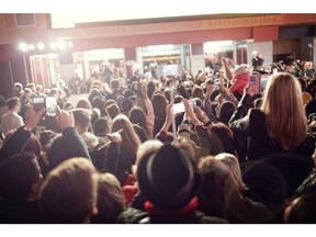 Crowd and fans taking photographs on mobile phones at a red carpet film premiere. Photo by Getty Images.