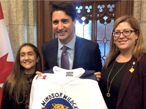 Jada Malott, a Grade 7 student at John Vianney school in Windsor, left, presents Canadian Prime Minister Justin Trudeau with a Windsor Wildcat hockey jersey during her visit to Ottawa on Oct. 5, 2016. Essex MP Tracey Ramsey is on the right.