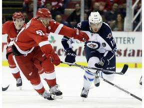 Detroit Red Wings centre Frans Nielsen, left, of Denmark, tries to chase down the puck against Winnipeg Jets centre Adam Lowry during an NHL game Friday, Nov. 4, 2016, in Detroit.