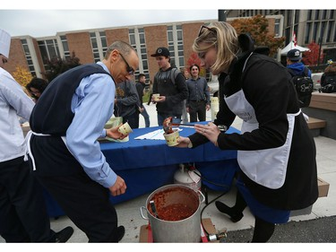 Ryan Kenney, left, and Gillian Heisz serve up chilli to students taking part in a free lunch at the University of Windsor in Windsor on Nov. 2, 2016. The event was hosted by the presidents office and featured vegetarian chilli, rolls, apples and hot chocolate. Staff served up the chilli to eager students as the Lancer Nation pep band provided music.