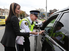 Jennifer Musson, left, and Ontario Provincial Police Staff Sgt. Ed Marocko talk with a motorist while launching the 2016 MADD Red Ribbon Campaign in Windsor-Essex. Musson's sister, Jessica Ondejko, was killed by a drunk driver in 2008. The 2016 MADD Red Ribbon Campaign was launched today along with area police forces at Anderson Funeral home in downtown Windsor.