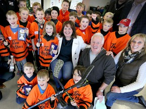 Carol Derbyshire, centre, of Hospice and Tim and Janet Beaulieu, right, co-chairs of Hockey for Hospice are surrounded by Tecumseh Orange Crush and Belle River Orange Flyers hockey players after they received trophies at Libro Complex Thursday Dec. 29, 2016.