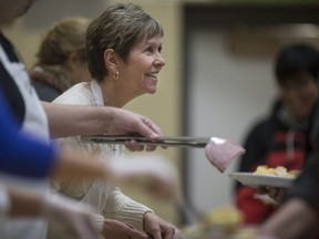 Volunteer Theresa Fortais, dishes out hot potatoes to those attending the Feeding Windsor program at St. Andrew's Presbyterian Church on Feb. 23, 2016.