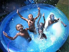 Chance Van Hoorn, 4, left, Julian Morgan, 4, Douth Jock, 6, and Lulu Jock, 6, splash and play while cooling off in Windsor on July 22, 2016.