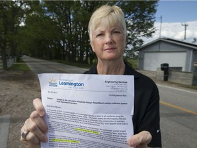 Gisele McLarty holds a notice from the Municipality of Leamington on May 30, 2017, notifying her that her bill will increase from $10,800 to $17,500 for sewer work outside her home on Point Pelee Drive.