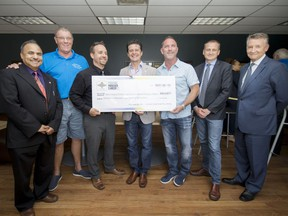 From left, Siyaram Pandey, Preston Harris, Shane Miles, Aldo DiCarlo, Ian France, Chris Houser, and Douglas Kneale hold a cheque as Pandey and his research lab receive funds from the Prostate Cancer Fight Foundation and TELUS Ride for Dad, at the University of Windsor on Tuesday, June 13, 2017.