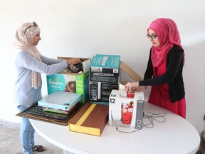 Volunteers Ghada Aljannati and Mahwish Ayub sort through donated items on May 31, 2017, for a new Muslim women's shelter in Windsor.