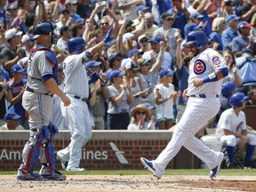 Chicago Cubs' Rene Rivera, right, scores on a three-RBI double hit by Albert Almora Jr. off Toronto Blue Jays' Marco Estrada during the third inning of a baseball game, Aug. 20, 2017, in Chicago.