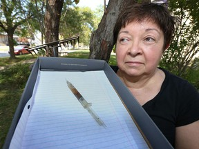 Peg Dorner keeps her distance from a dirty hypodermic needle  she found Saturday morning while dethatching her lawn.