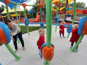 Rachel Trella, left, and her four-year-old triplets Olivia, Hailey and Ava try out the Play McGivney facility on Wednesday. The yard between the John McGivney Children's Centre and Hotel-Dieu Grace Healthcare has been transformed into an accessible outdoor space for those of all ages.