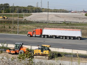 Heavy equipment sits on the side of Ojibway Parkway where an overpass will be constructed over Ojibway Parkway to connect the Herb Gray Parkway to the Gordie Howe Bridge plaza location, seen in the top of the photo.