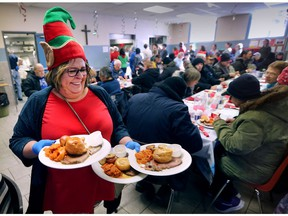 The Downtown Mission served a special Christmas meal on Thursday, Dec. 14, 2017 to members of the community who are struggling with poverty and homelessness. Volunteer server Laurie Musson delivers plates to guests during the meal.